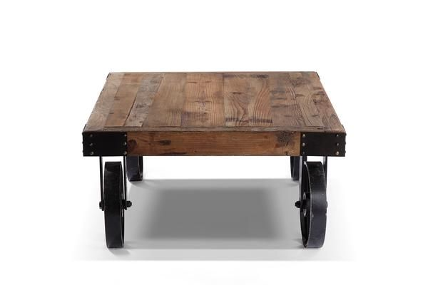 La table basse à roulettes possède un design industriel. Constituée d'un plateau de bois brut et de roues en fer, elle rappelle l'esprit d'un chariot de train.