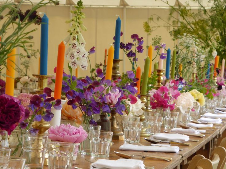 Flowers, coloured candles and place settings in a marquee in Dorset, southern England for the summer wedding of design duo Charlie McCormick & Ben Pentreath