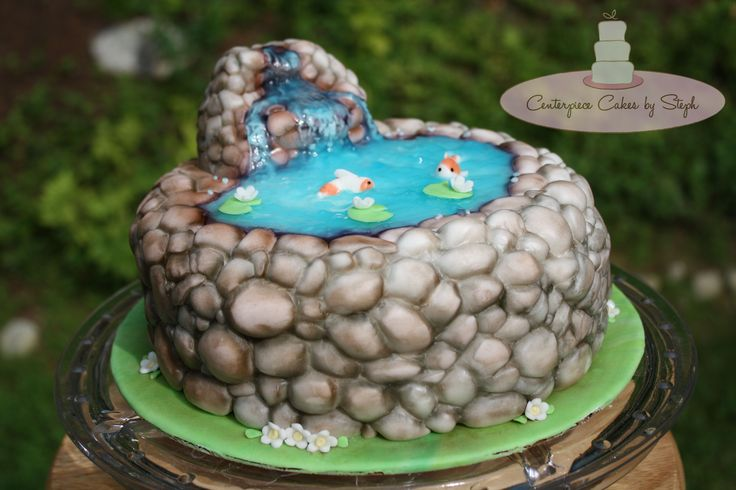 """- This 8"""" Chocolate cake was a surprise Birthday cake for a very special wife.. Her husband had this amazing idea that he wanted to surprise her with a beautiful yet peaceful backyard pond cake and to my surprise he provided me with a very detailed sketch!! Pretty sure he just might have a side job if he needs one LOL ;)  Every stone was hand made out of fondant, the waterfall is made out of rice krispy treats. The Koi & decorations are all fondant, the water is home made sugar gel. ♥"""