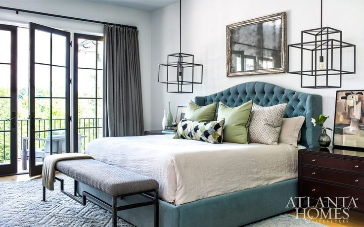 The master bedroom overlooks the scenic countryside; the room is punctuated with an antique silver-framed mirror and iron chandeliers that serve as bedside lamps.