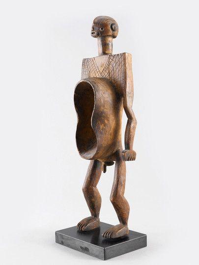 KORO FIGUR Nigeria. H 59 cm. Diese figürlichen Gefässe kamen anlässlich von Gedenkfeiern und insbesondere bei Begräbnissen zum Einsatz. Die erdnussförmige Schale im Bauch der Figur diente ganz natürlich zur Aufnahme von Flüssigkeiten (Palmwein oder Hirsebier usw.) oder rituellen Speisen.