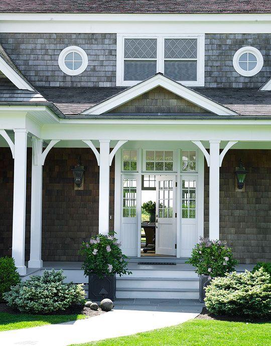 Cedar shake siding, white trim, round porthole windows, transom lite door, porch post braces.