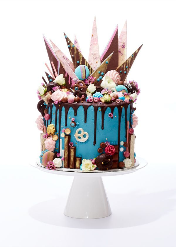Candy explosion drip cake similar to the Black Tap milkshakes. White chocolate bark, pretzels, macarons, candy, chocolate drip, meringues, all on cake with blue buttercream frosting. Inspired by Katherine Sabbath.