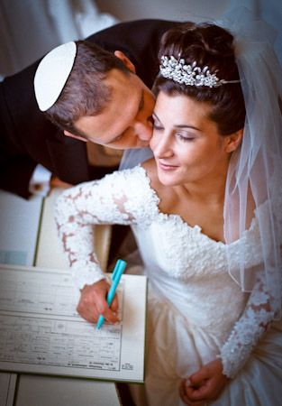 Beautiful picture to take for a wedding Jewish bride and groom signing the ketubah
