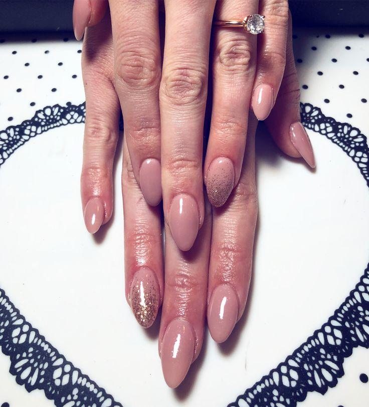 Blush almond acrylic nails with glitter.