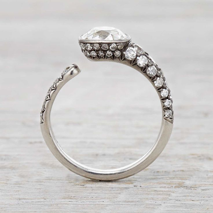 Serpentine engagement ring made in platinum with black rhodium and centered with an antique old mine cushion cut diamond made by Erstwhile