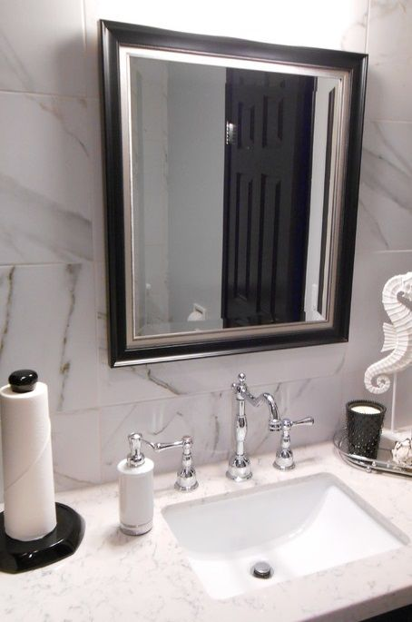 stunning luxury modern bathroom of los alamitos with black vanity with marble countertop and framed wall