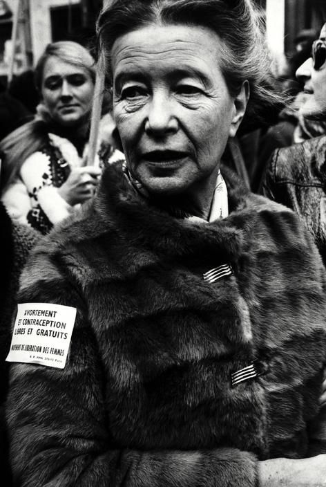 "Simone de Beauvoir during a women's demonstration in Paris. The text in her arm says: ""Free and costless abortion and contraception. Women's Liberation Movement"". Paris, 1971. Photo: Gilles Peress."