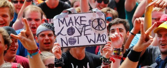 """A festival goer holds up a sign that reads """"make love not war"""" as the crowd cheers for a rock band at the open-air weekend """"Rock am Ring"""" concert at Germany's Formula One race track Nuerburgring, Germany June 3, 2017. REUTERS/Wolfgang Rattay"""