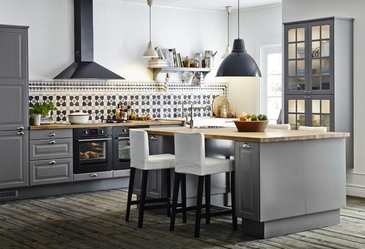 cuisine élégante aménagée avec des armoires grises, un îlot en gris et bois et des plans de travail en bois
