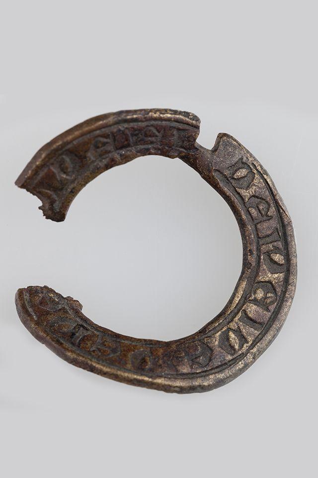 Ta wykonana z brązu zapinka kolista tzw. maryjna, używana była przez pielgrzymów do spinania odzieży pątniczej. Okaz ten o średnicy ok. 3,5 cm jest rozerwany, lekko zdeformowany i brakuje mu kolca. Pochodzi z XIII w., został znaleziony na ul. Warszawskiej w Gnieźnie w pobliżu kościoła farnego. Znajdująca się w otoku inskrypcja łacińska, napisana czcionką gotycką, to 6-krotne powtórzenie słowa Bóg (Dei).