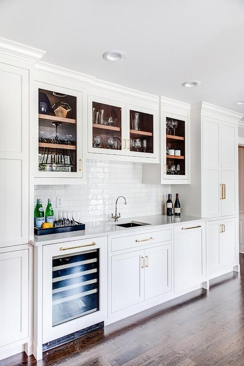 Glass cabinets over a square wet bar with sink featuring white linear subway tiles with a glossy finish.