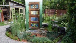 Grästrädgård med färggrannt målad dörr som portal i mitten