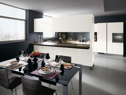 """This composition, with gloss White lacquered doors 29 mm thick, includes a combination of wall units and  peninsula, and uses a sliding glass partition to separate the working area of the kitchen from the living zone. The """"Mirage"""" partition viewed from the  kitchen's working and service zone.  There are no handles in the door front  panels; in the modern Scenery kitchen,  the units are opened by means of  handles set into the tops or sides of the  fronts, or by grooves."""