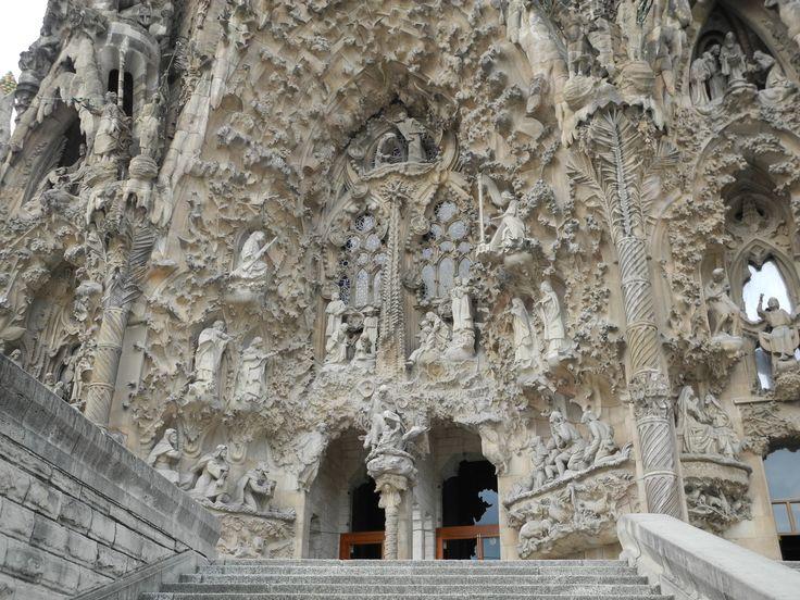 PUERTA DEL NACIMIENTO La fachada del Nacimiento, también llamada de Levante, es la única construida en vida de Gaudí. Al centro, sobre la puerta principal y entre las cuatro torres, se encuentra un ciprés que representa el árbol de la vida, coronado con una cruz en forma de T , simbolizando al Dios Padre, con unas diagonales encima en forma de X que representa el símbolo del nombre de Cristo y una paloma con las alas abiertas en alusión al Espíritu Santo.