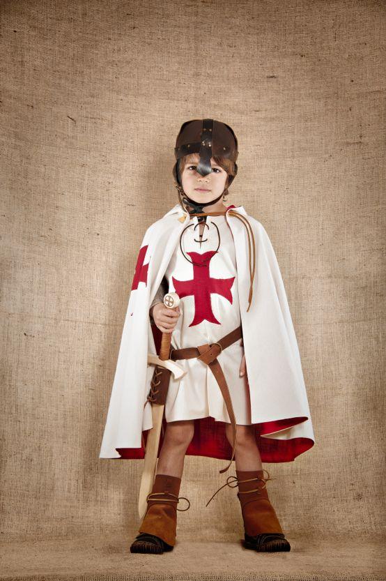 """Costume médiéval de chevalier templier inspiré des croisés du 13ème siècle composé de 3 pièces : La tunique en coton est munie de manches matelassées en lin amovibles, la cape entièrement doublée en coton avec capuche et galon de cuir et enfin la cale sorte de petite coiffe en lin gris chiné. Ce costume de fabrication artisanale est disponible du 4 au 12ans. Tous les accessoires en cuir et en bois sont également disponibles sur le site de """"7 et une Lieues"""""""