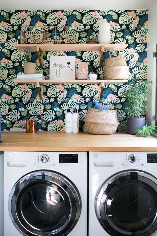 Gorgeous wallpapered laundry room looks so chic with open shelving and counter above white front load washer and dryer.