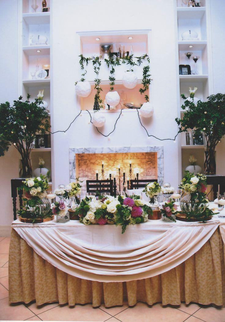【ホワイトとグリーンがテーマの結婚式】披露宴会場 ポイントで青みのピンク色 キャンドル 電球 丸いランタン 大きな木 幻想的 結婚式 高砂 装飾