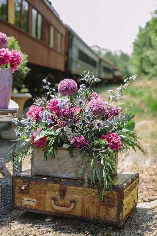 old suit cases purple wedding flowers