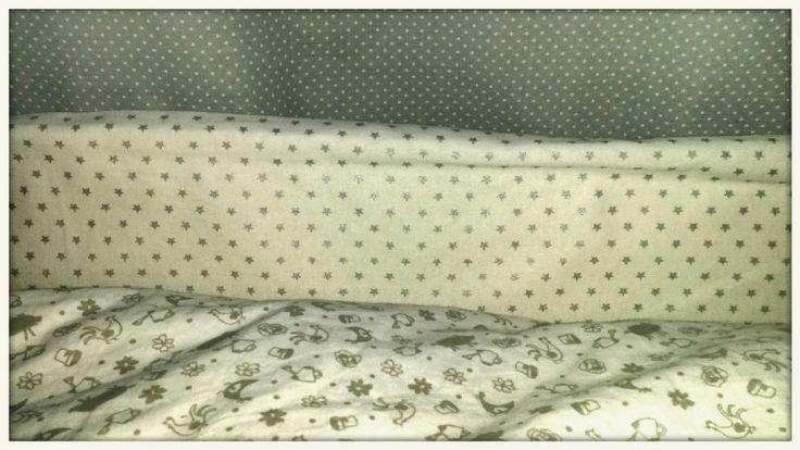 Tessuti grigio e bianco per camerette. Tende grigie a pois, paracolpi bianco con stelline grigie e copripiumone con figure grigie tortora