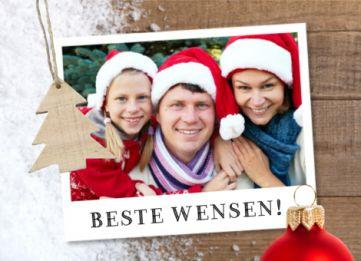 Kerstkaart met winters tintje. Een houten kerstboomlabel, rode kerstbal en je eigen foto in een polaroid kader