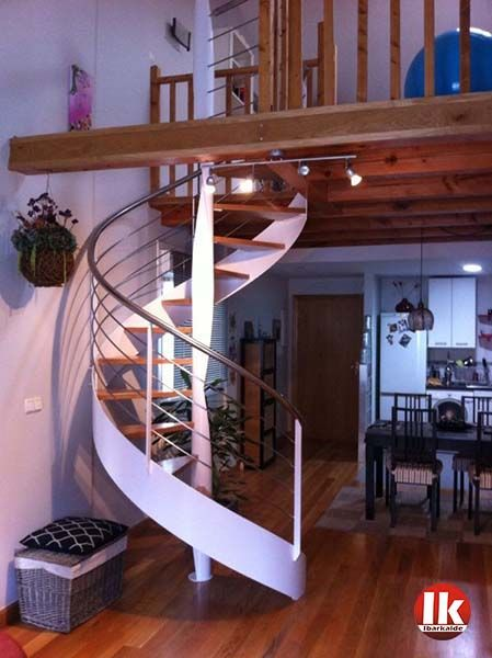 escalera de caracol de estructura metlica y peldaos de madera lacada en blanco