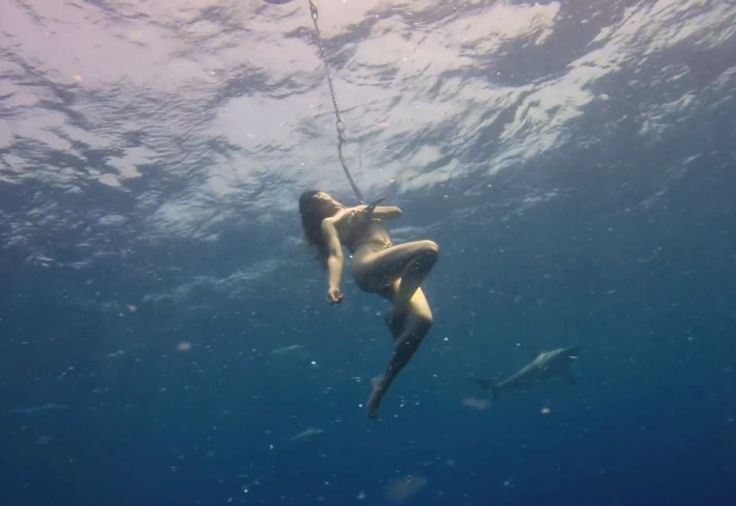 Find out why this woman hung naked from a hook surrounded by sharks