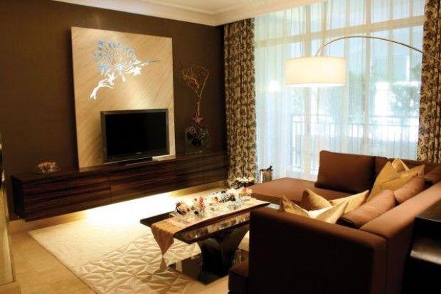 Il mobile porta tv in ebano e il divano cioccolato ravvivati dalla pavimentazione e dai complementi tendenti all'oro