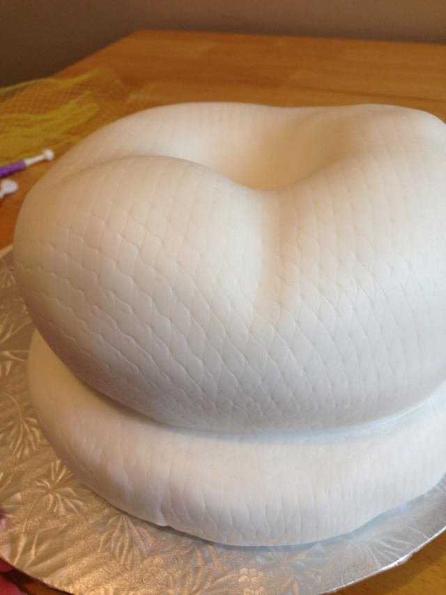 "Lightly spritz the ganached cake with a mist of water, and put your fondant over the cake, carefully pressing it into the ""snake coils"" and any crevices you've created to add definition to your cake."