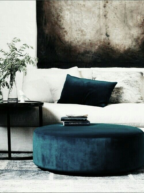 Teal ottoman and pillow with white sofa and charcoal abstract art