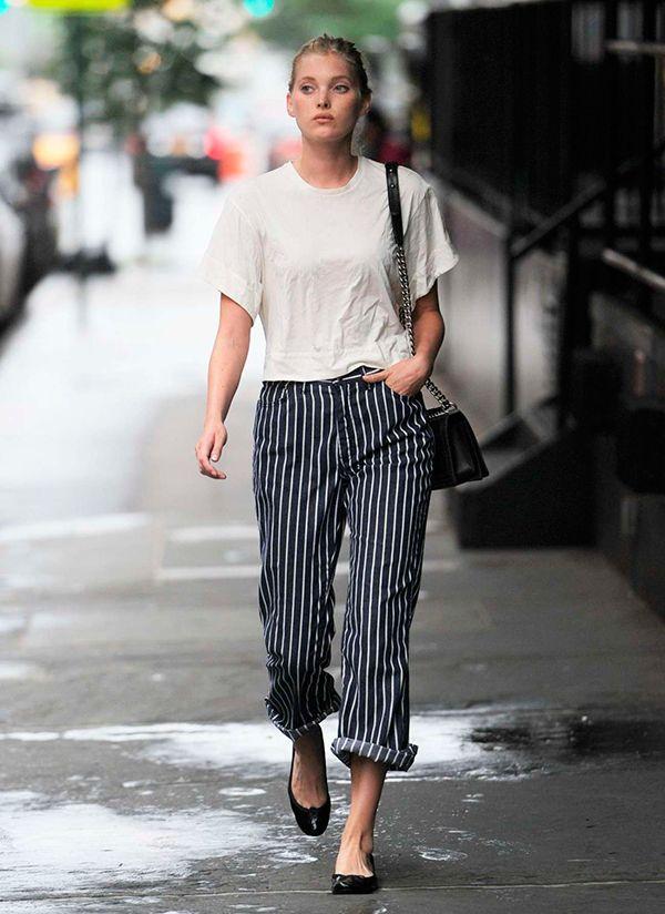 Elsa Hosk anda pela calçada de Nova York usando blusa off white, calça de alfaiataria risca de giz, bolsa preta e sapatilhas pretas