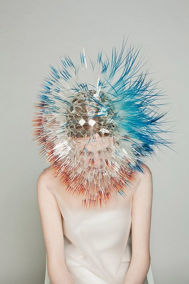"""Atmospheric Reentry"", recently presented at Royal College, is the new way of conceiving female head pieces, signed Maiko Takeda: Maiko developed an experimental architecture, so that each quill, printed with color on transparent film, is supported by acrylic disks, that are in turn sustained by a grid of silver rings."