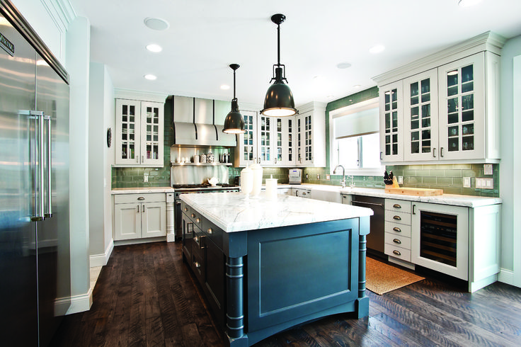 A large island, adorned with a gorgeous slab of white Carrara marble, creates a highly functional and elegant kitchen.