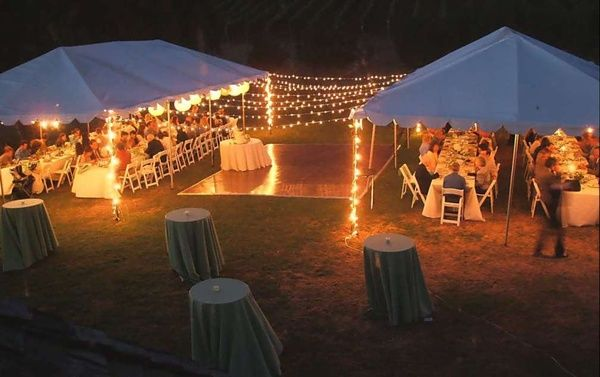 Backyard wedding tents, globe lights over dance floor, cocktail tables and guest settings.