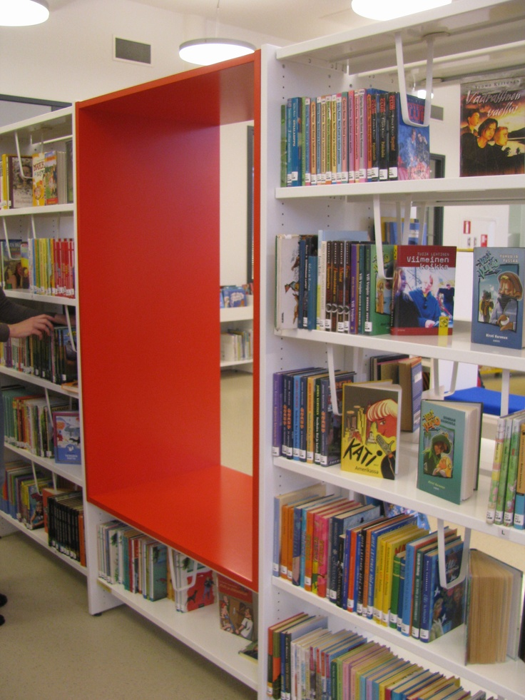 Ritaharju joint-use library, Oulu. The non-fiction shelves house material for younger people on the lower shelves and for adults on the top shelves. The shelves have red openings for sitting and browsing.