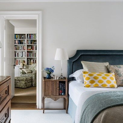 Bedroom with wooden furniture and velvet headboard in Bedroom Decoration Ideas. Modern white bedroom with wooden drawers and bedside table and turquoise bed linen.