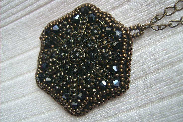 Ny-556. Fekete és bronz színű, fém alapon gyöngy-hímzett medál, bronz színű hosszú láncon. A nyaklánc hossz: 2 x 36 cm. A medál mérete: 52 x 49 mm. Ára: 890.-Ft.