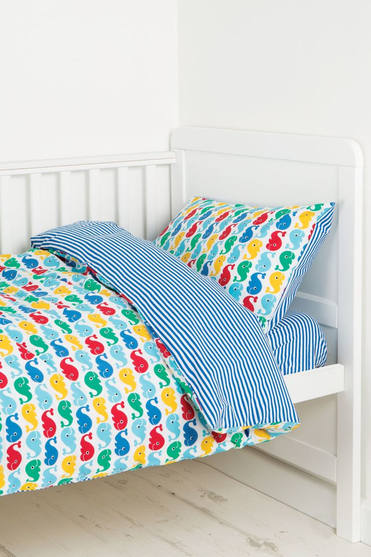 Surround your little one in super soft, chemical free organic cotton! Made from 100% organic cotton in a fun and colourful all over Frugi print with a matching striped reverse. This Cosy Cot Bed Set contains a reversible printed duvet cover, one reversible pillow cover, a stripy fitted sheet and lush coloured button fastenings. All beautifully presented in an organic cotton drawstring bag in a matching print, perfect for a fully Frugi coordinating bed! Pillow cover: 60cm x 40cm, Duvet cover…