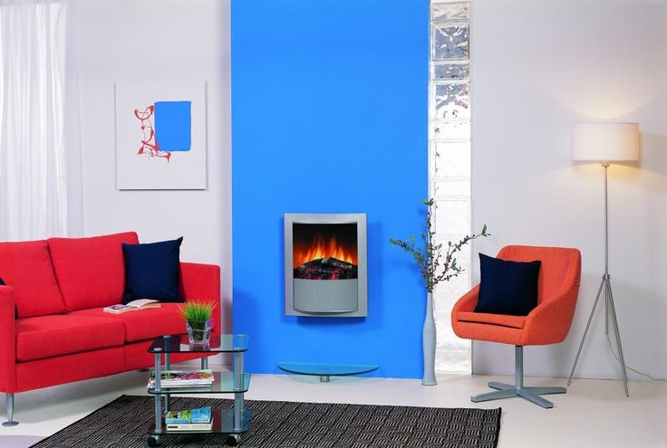 http://www.drissimm.com/wp-content/uploads/2014/12/elegance-electric-fireplace-set-on-blue-wall-idea-with-orange-fabric-sofa-in-the-near-and-small-glass-table-on-rug-along-with-lamp-standing-on-floor-and-black-cushions-on-sofa.jpg