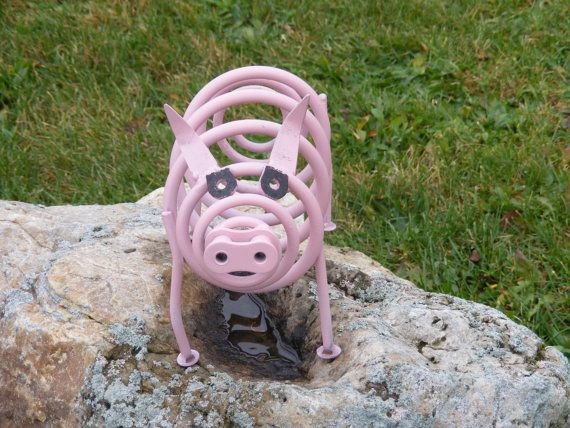 This cute little pink pig is made from an old car spring, some discarded bolts, a piece of industrial roller chain, and a pair of old garden