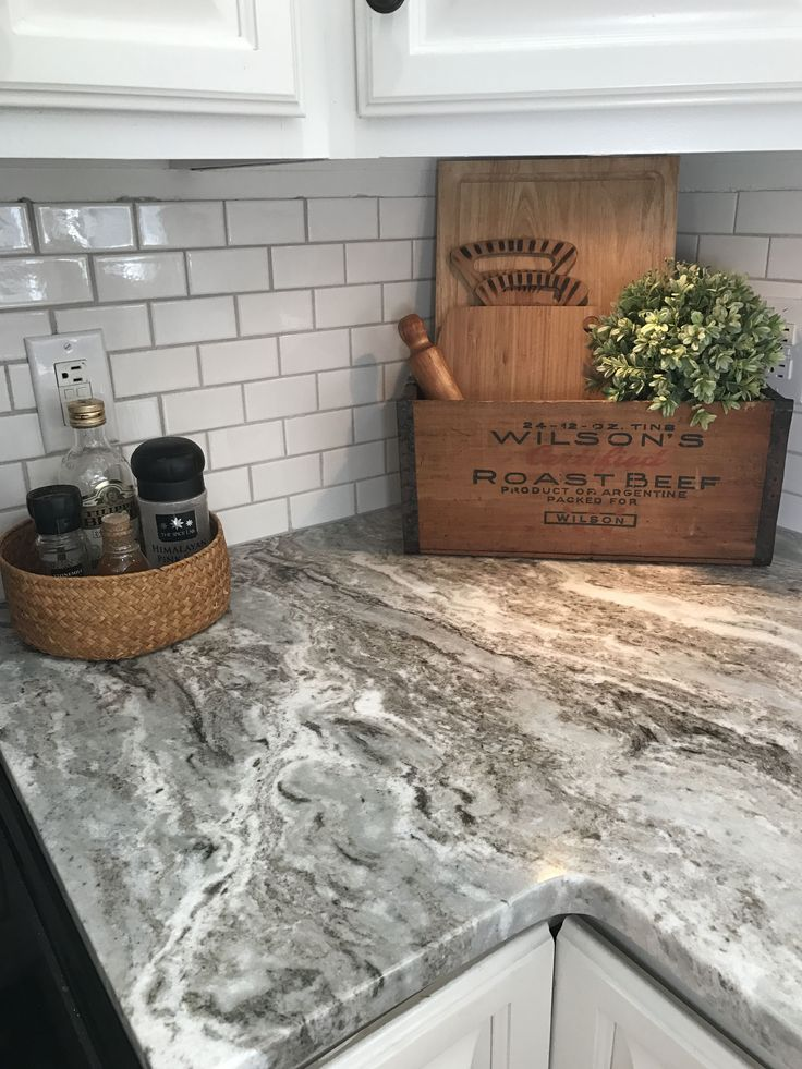 Fantasy brown granite with small white subway tiles.