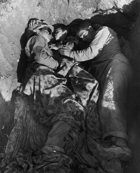 A pair of US Marines share their foxhole with an Okinawan boy who wandered into their lines, July 1945