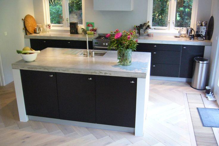 Zwarte keuken met wit en beton.