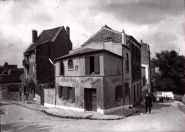 """La Maison Rose, 2 rue de l'Abreuvoir, fin des années 1920. Elle existe toujours, la Maison Rose, et c'est toujours un restaurant. Les façades des immeubles mitoyens ont été quelque peu modifiées. C'est Laure «Germaine » Gargallo, ancien modèle de Picasso lors de sa période bleue, et son mari le peintre Ramon Pichot, qui ont ouvert """"La Maison Rose"""", vers 1905. Cette maison aux murs peints, a été rendue célèbre par le tableau qu'en a fait Maurice Utrillo."""