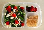 Spinach salad with feta cheese, almonds, grape tomatoes.  Strawberries, turkey and cheese rolled in a whole wheat flour tortilla.