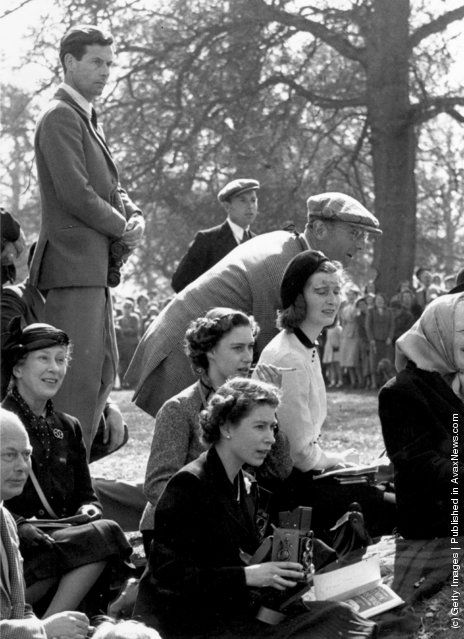 Queen Elizabeth II holding a camera at the Olympic Horse Trials at Badminton, whilst Princess Margaret (1930–2002) sits behind her, smoking a cigarette and watching the action. Also in the group is Group Captain Peter Townsend (left). (Photo by Reg Birkett/Keystone/Getty Images). 13th October 1955