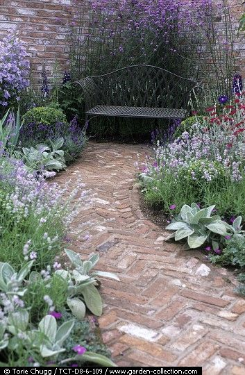 Herringbone brick path with silver/blue/white plants: Possibility for front walkway on either side of brick/tile leading to front door.