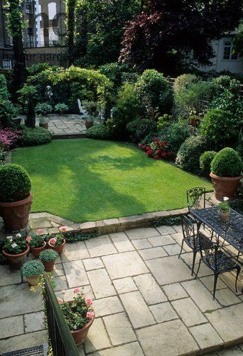 Harpur Garden Images Ltd :: CM200 Small formal town garden with paved patio, dining table and chairs, lawn, containers, borders, arch dividing separate patio at far end of garden. Christopher Masson, London Mrs Kalborg Jerry Harpur Please read our licence terms. All digital images must be destroyed unless otherwise agreed in writing. Photograph by: www.harpurgardenl... Contact: Harpur Garden Library 44 Roxwell Road Chelmsford Essex CM1 2NB, UK