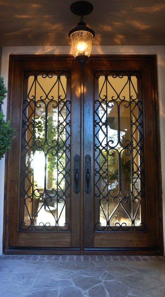 The Puerta Albanico is a pair of Spanish entry doors featuring hand-forged iron scrollwork placed over glass panels.