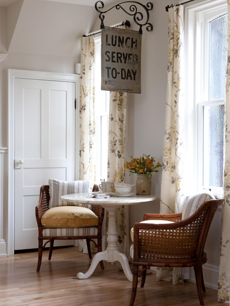 A white bistro table sits beneath a vintage restaurant sign in this kitchen breakfast nook. Rattan armchairs and white floral curtains complete the casual feel.